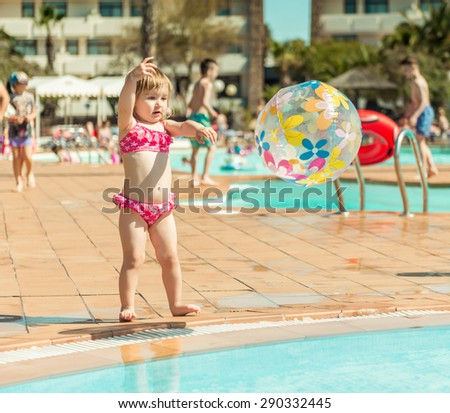little cute girl playing near the pool with a ball - stock photo