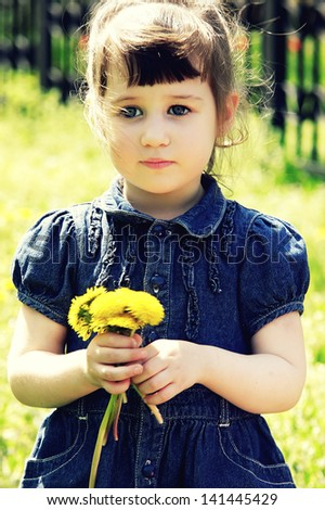 Little cute girl playing on the meadow with dandelions
