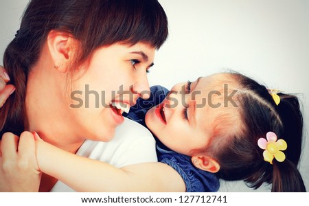 little cute girl playing with her mother - stock photo
