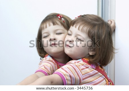 little, cute, girl playing with her twin in the mirror
