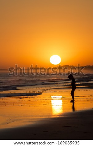 Little cute girl playing with the waves on the beach on a orange sunset.