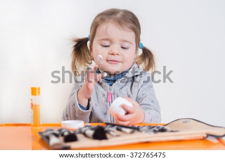 Little cute girl puts on face cream on the white background