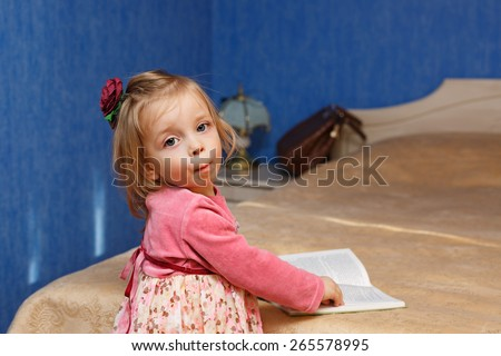 Little cute girl reading a book in the bedroom. The concept of education in the preschool years. - stock photo