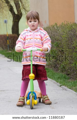 little, cute girl riding a scooter on a spring day