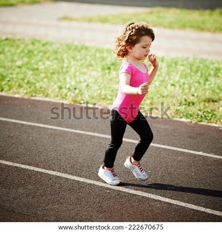 little cute girl running at stadium - stock photo
