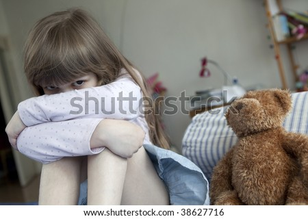 little cute girl seven years old  sitting on bed and crying - stock photo