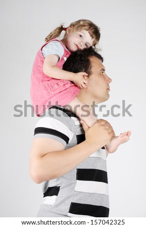 Little cute girl sits on shoulders of her father on grey background.