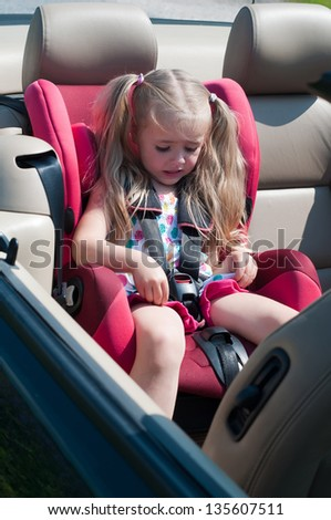Little cute girl sitting in car seat - stock photo
