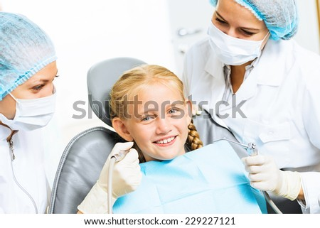 Little cute girl sitting in chair at dentist - stock photo
