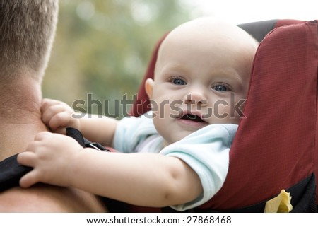 little cute girl sitting in sling holding for father shoulders. Summer time - stock photo