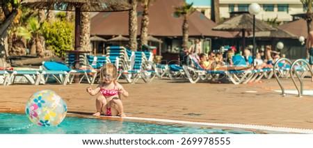 little cute girl sitting near the pool with a ball. panoramic framing - stock photo