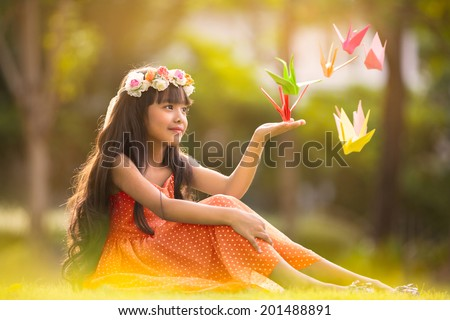 Little cute girl sitting on grass in park with origami cranes, Outdoor portrait - stock photo