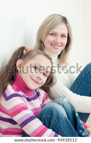 Little cute girl sitting on the floor with her mom, smiling and looking at camera
