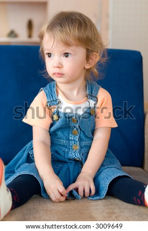 little cute girl sitting on the sofa.