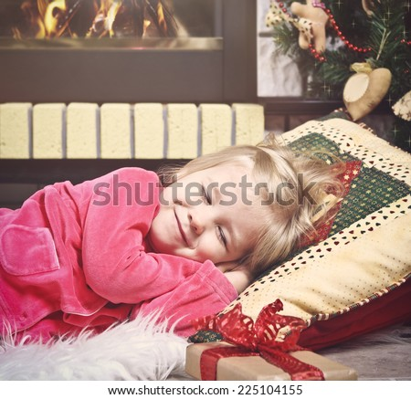 Little cute girl sleeping under the Christmas Tree waiting for Santa Claus to come - stock photo