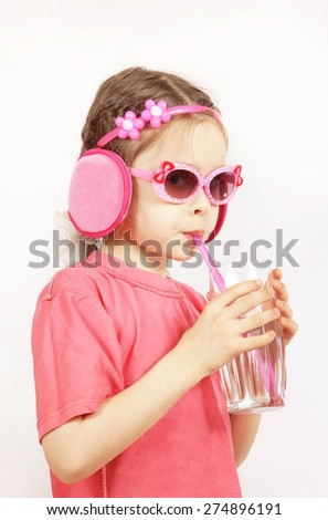 Little cute girl wearing pink clothes is drinking water from the glass with a pipe - stock photo