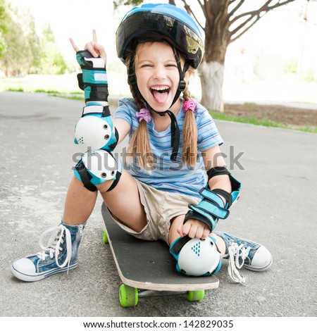 little cute girl with a helmet sitting on a skateboard - stock photo