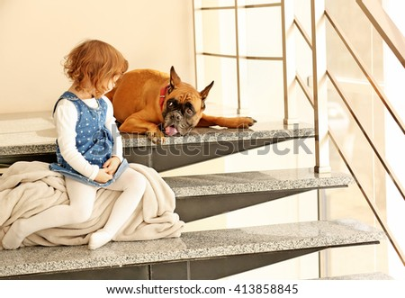 Little cute girl with boxer dog sitting on the stairs indoor - stock photo