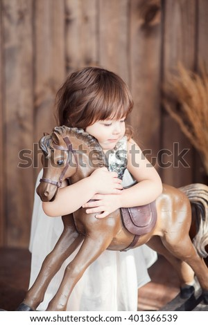 little cute girl with brown hair in a white dress hugging a horse rocker, a look to the side, tenderness - stock photo