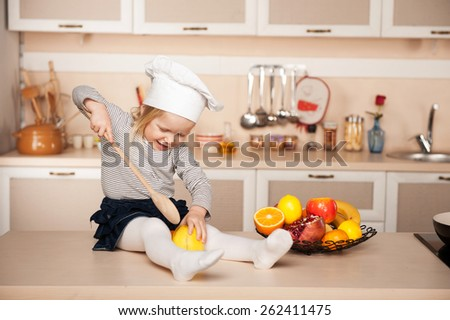 Little cute girl with chef hat holding big wooden spoon while cooking. Kitchen interior. Concept for young kitchen hands - stock photo