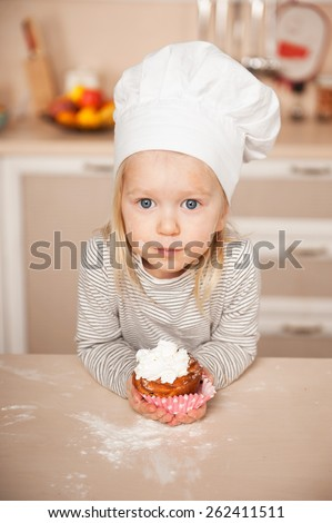 Little cute girl with chef hat holding cake and looking at camera. Kitchen interior. Concept for young kitchen hands - stock photo
