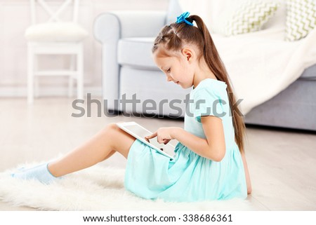Little cute girl with digital tablet sitting on carpet, on home interior background