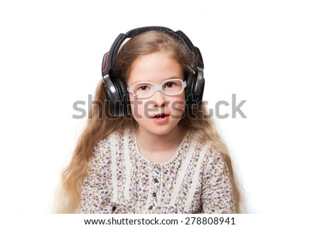 little cute girl with glasses and headphones listening to music - stock photo