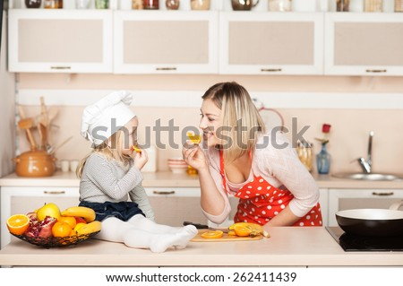 Little cute girl with her mother eating orange while cooking. Kitchen interior. Concept for young kitchen hands - stock photo