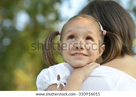 Little cute girl with her mother in park