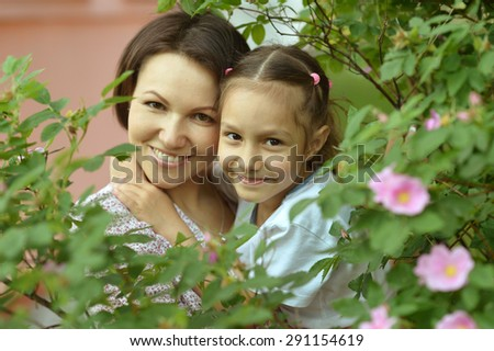 Little cute girl with her mother in summer park - stock photo