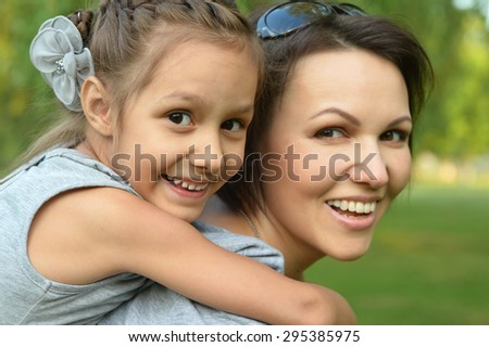 Little cute girl with her mother in summer park
