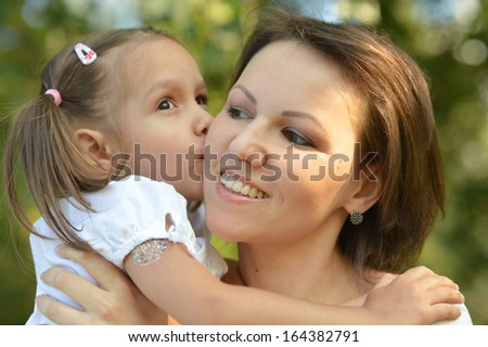 Little cute girl with her mother on the walk - stock photo