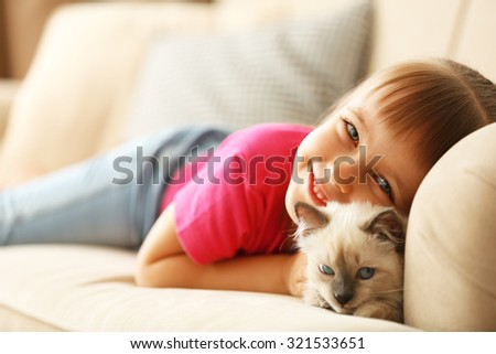 Little cute girl with kitten on sofa at home - stock photo