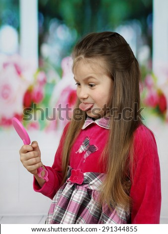 Little cute girl with long hair shows her tongue in mirror - stock photo