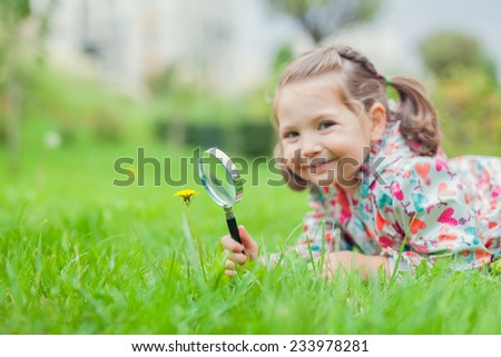 Little cute girl with magnifier looking at flower. - stock photo