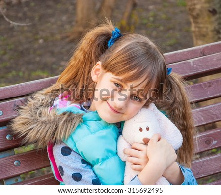 Little cute girl with pigtails with a toy in the hands on a park bench