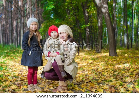 Little cute girls and young mother in autumn park have fun - stock photo