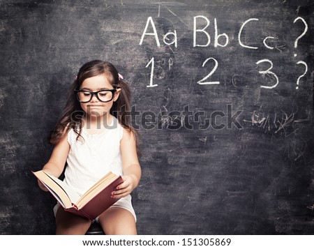 little cute girls looking for answers in front of blackboard - stock photo