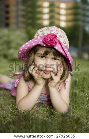 little cute gloomy girl in panama lying on grass