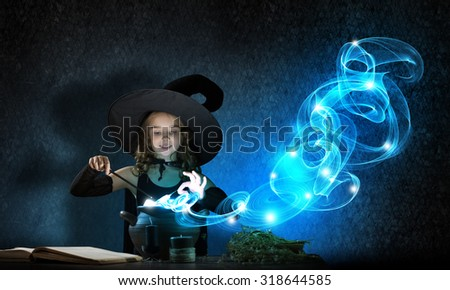 Little cute halloween witch reading spell above pot - stock photo