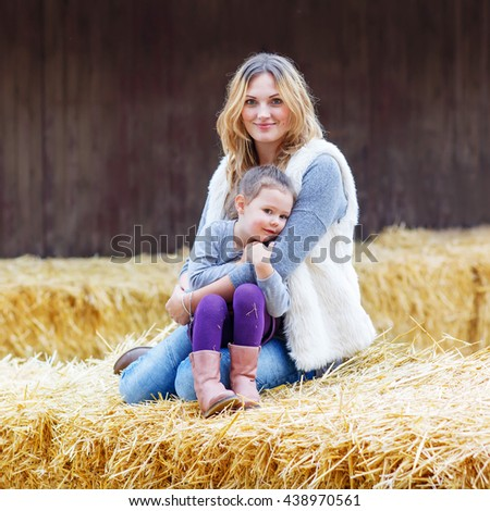 Little cute happy girl and beautiful woman having fun with hay on a farm. Family of two enjoying autumn season and laughing. Happy childhood, family, lifestyle concept. - stock photo