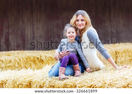 Little cute happy girl and her mother having fun with hay on a farm. Family of two enjoying autumn season and laughing. Happy childhood, family, lifestyle concept. - stock photo