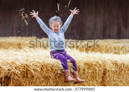 Little cute happy girl having fun with hay on a farm. Child enjoying autumn season and laughing. Happy childhood, lifestyle concept. - stock photo