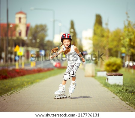 little cute happy girl rollerblading through the city streets - stock photo