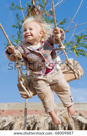 Little cute happy girl swinging outdoors in sunlight - stock photo