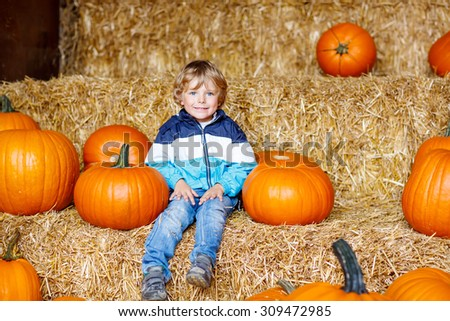 Little cute kid boy sitting with huge pumpkin on halloween or thanksgiving harvest festival or patch, outdoors - stock photo