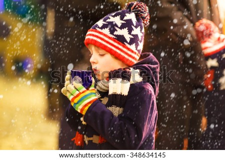 Little cute kid boy with cup of steaming hot chocolate or children punch. Happy child on Christmas market in Germany. Traditional leisure for families on xmas - stock photo