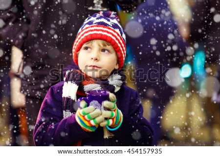 Little cute kid boy with cup of steaming hot chocolate or children punch. Happy child on Christmas market in Germany. Traditional leisure for families on xmas
