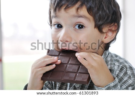 Little cute kid eating chocolate - stock photo