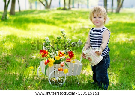 Little cute kid in the garden with watering can and spring flowers in the wooden decorative wheelbarrow